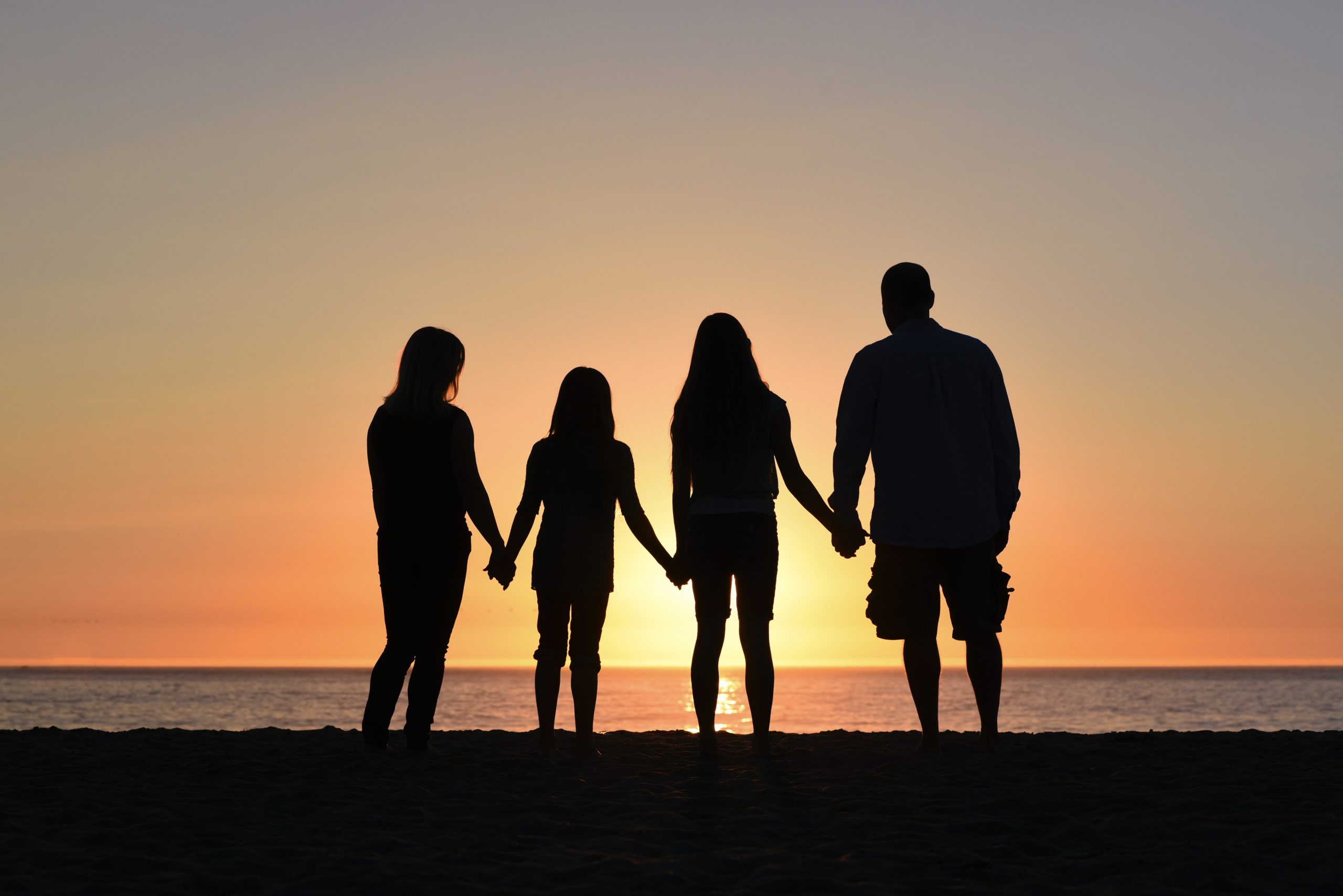 Family on beach holding hands watching sunset.