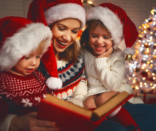 Mother with son and daughter (wearing Santa hats) on lap reading a Christmas story.