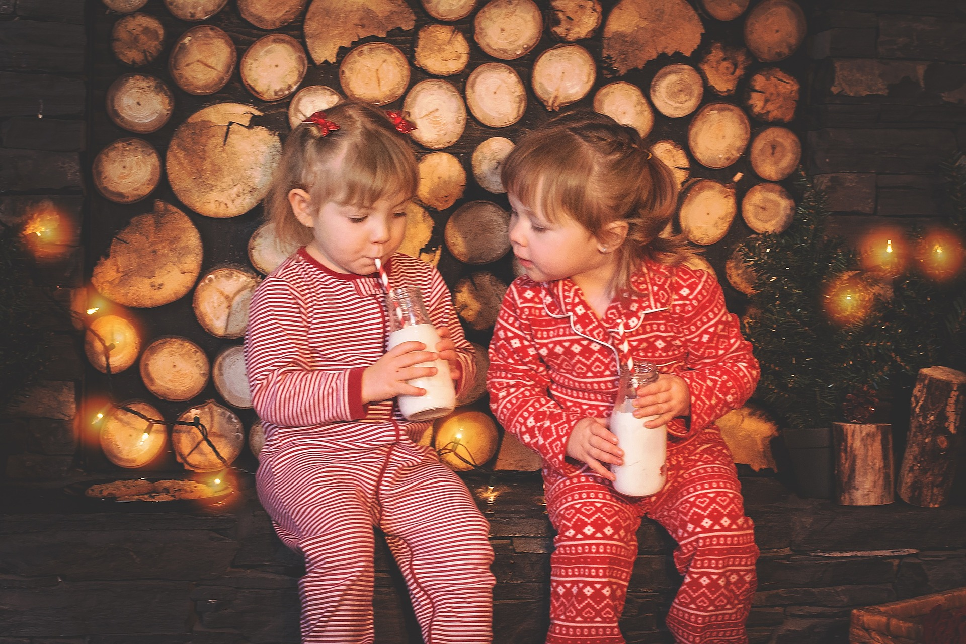 Two little girls dressed in Christmas pajamas drinking milk.