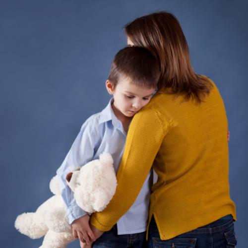 Mother hugging little boy with teddy bear.